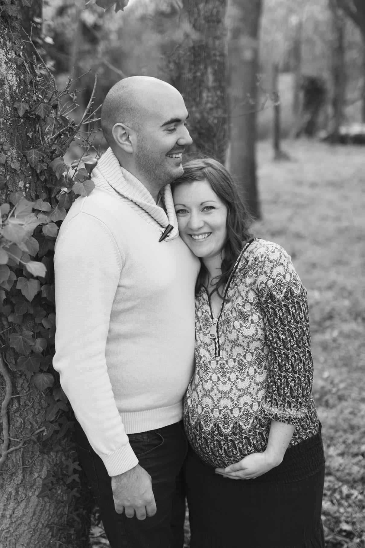 Photo en noir et blanc du couple se tenant contre un arbre
