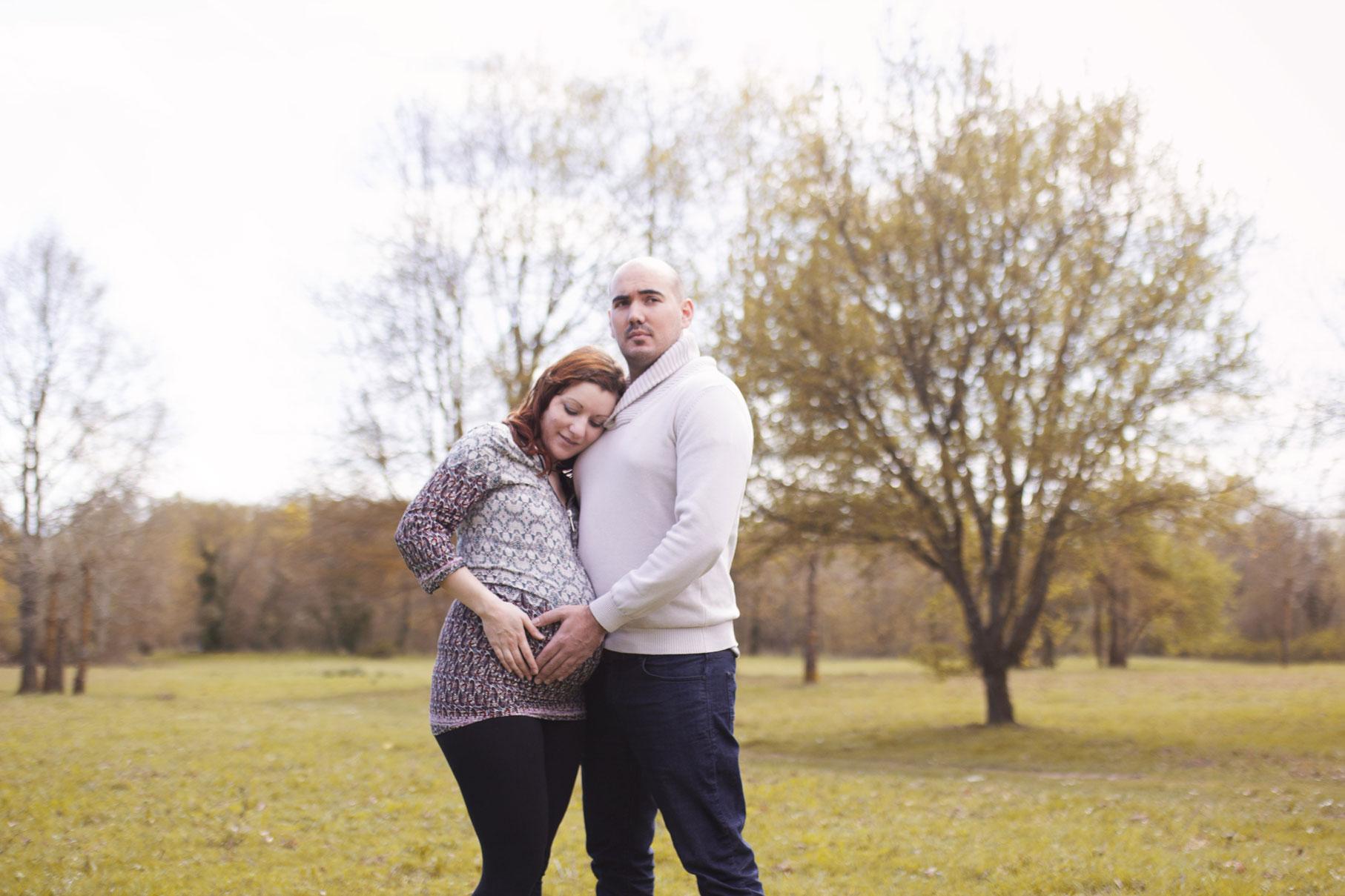 Couple enlacé formant un coeur de leurs main sur le ventre de la femme enceinte