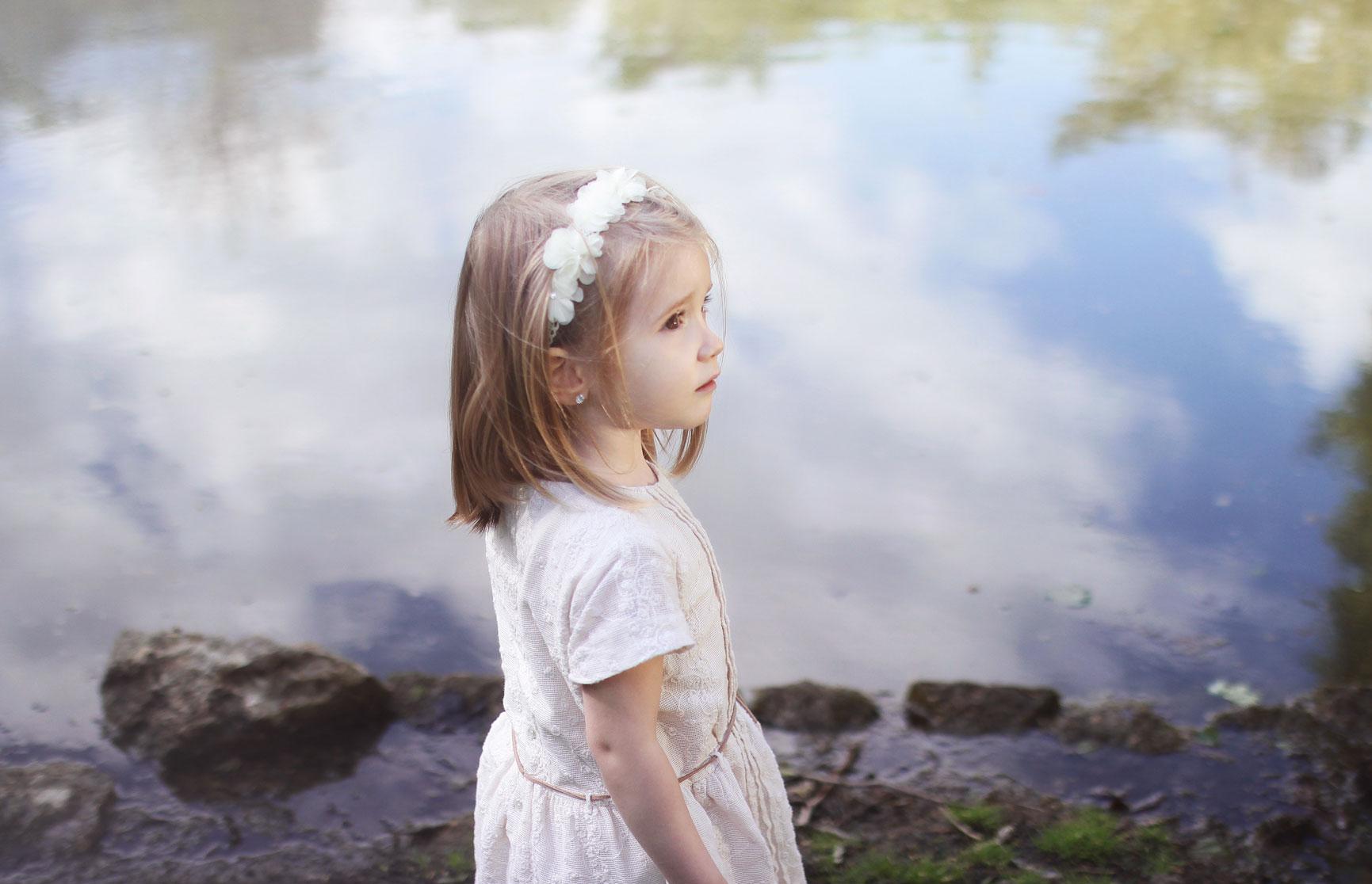 Une petite fille au bord de l'eau avec une jolie robe blanche et des fleurs dans les cheveux