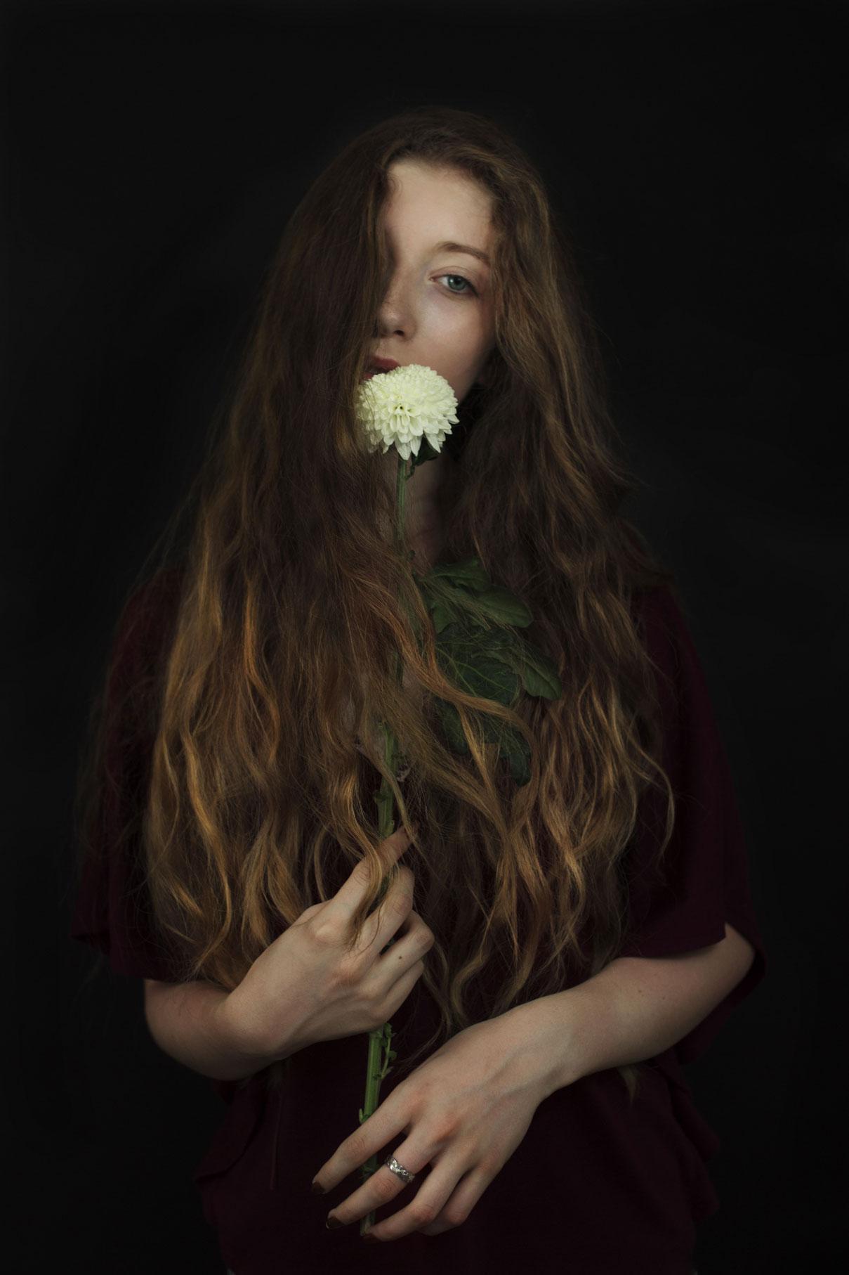 jeune femme aux long cheveux blond vénitiens avec une fleur blanche