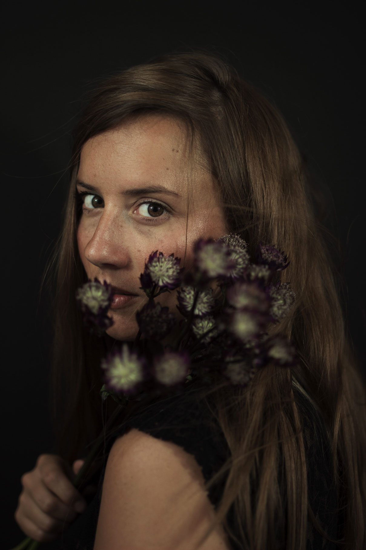jeune femme au regard profond avec des fleurs de chardons.