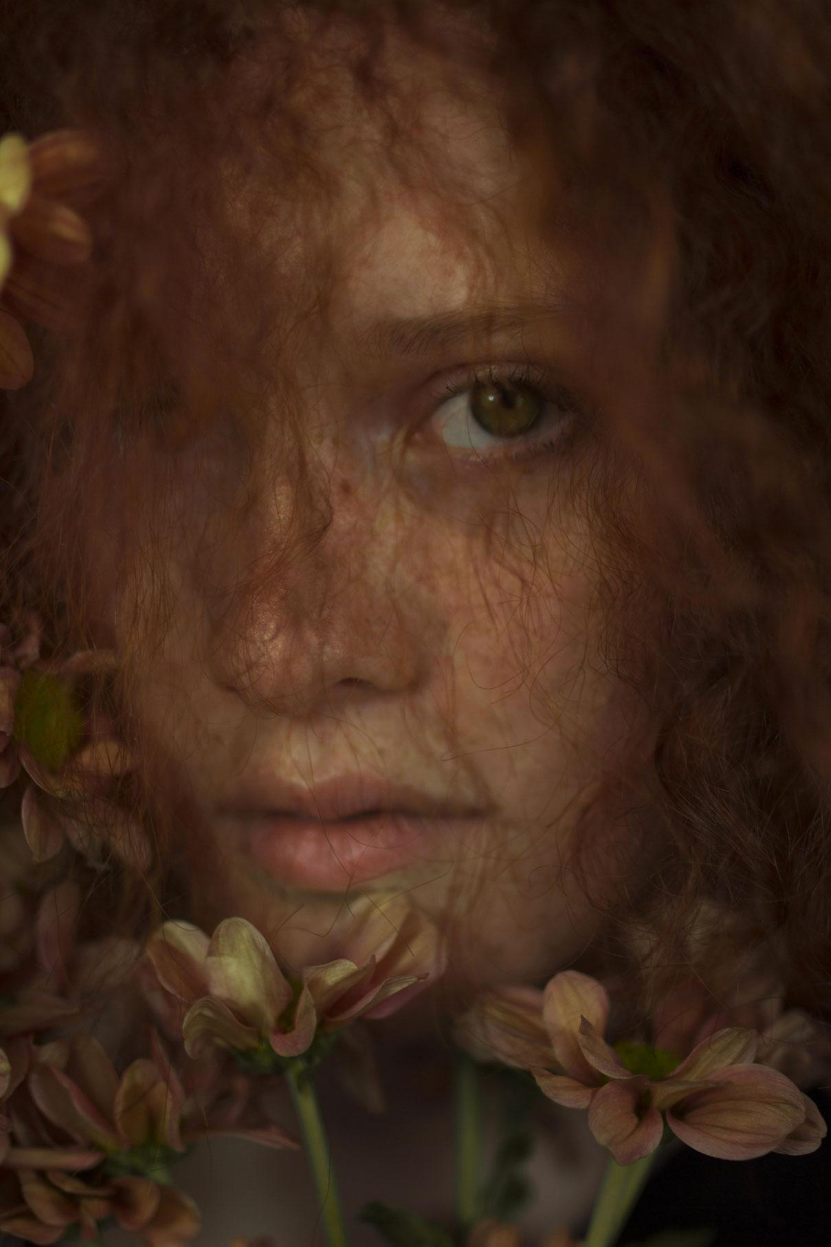 Photo de portrait d'une demoiselle rousse au milieu des fleures