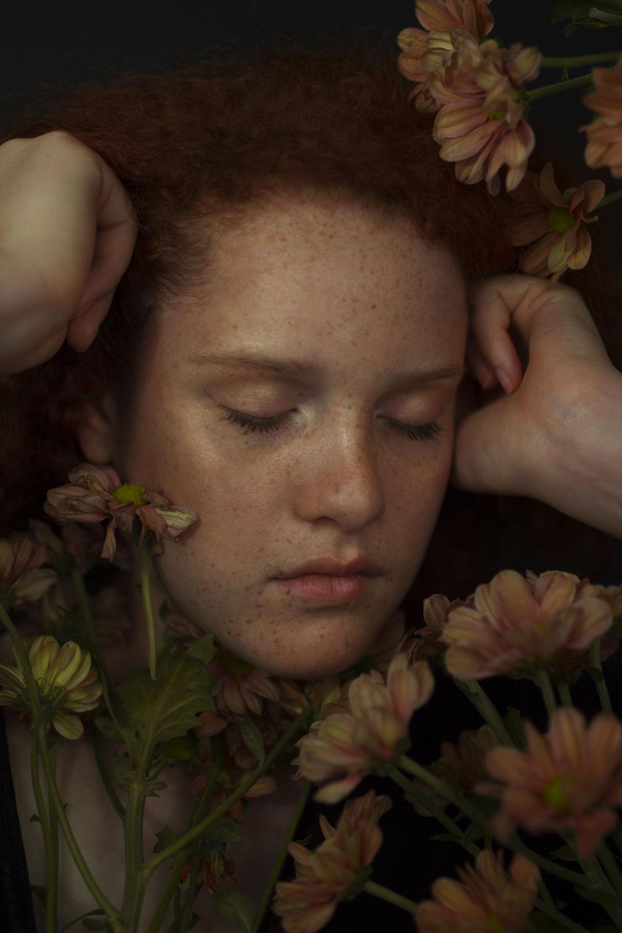 Photo de portrait d'une demoiselle rousse au milieu des fleures fermant les yeux