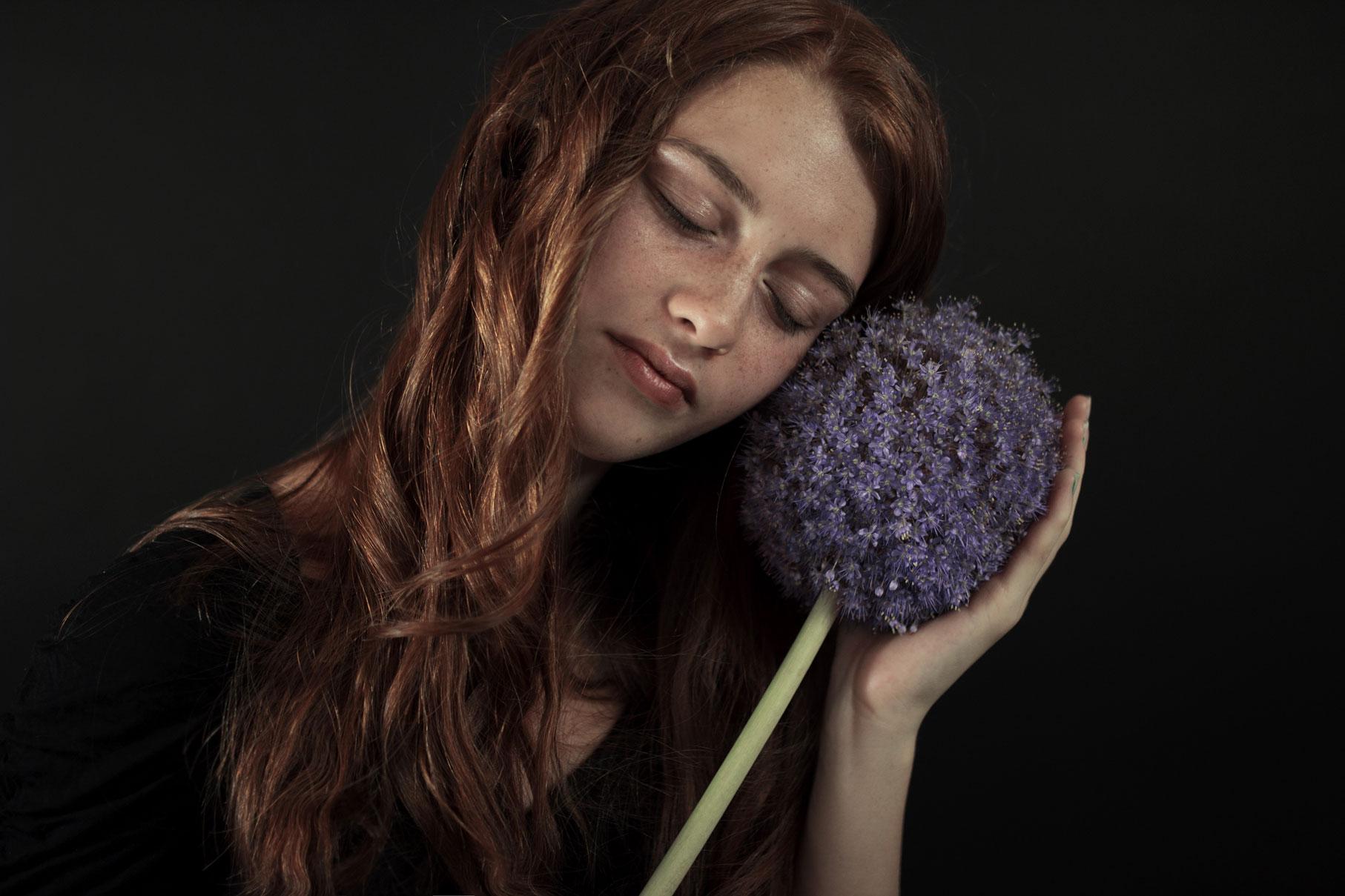 Jeune fille les yeux fermés avec des fleurs violettes.