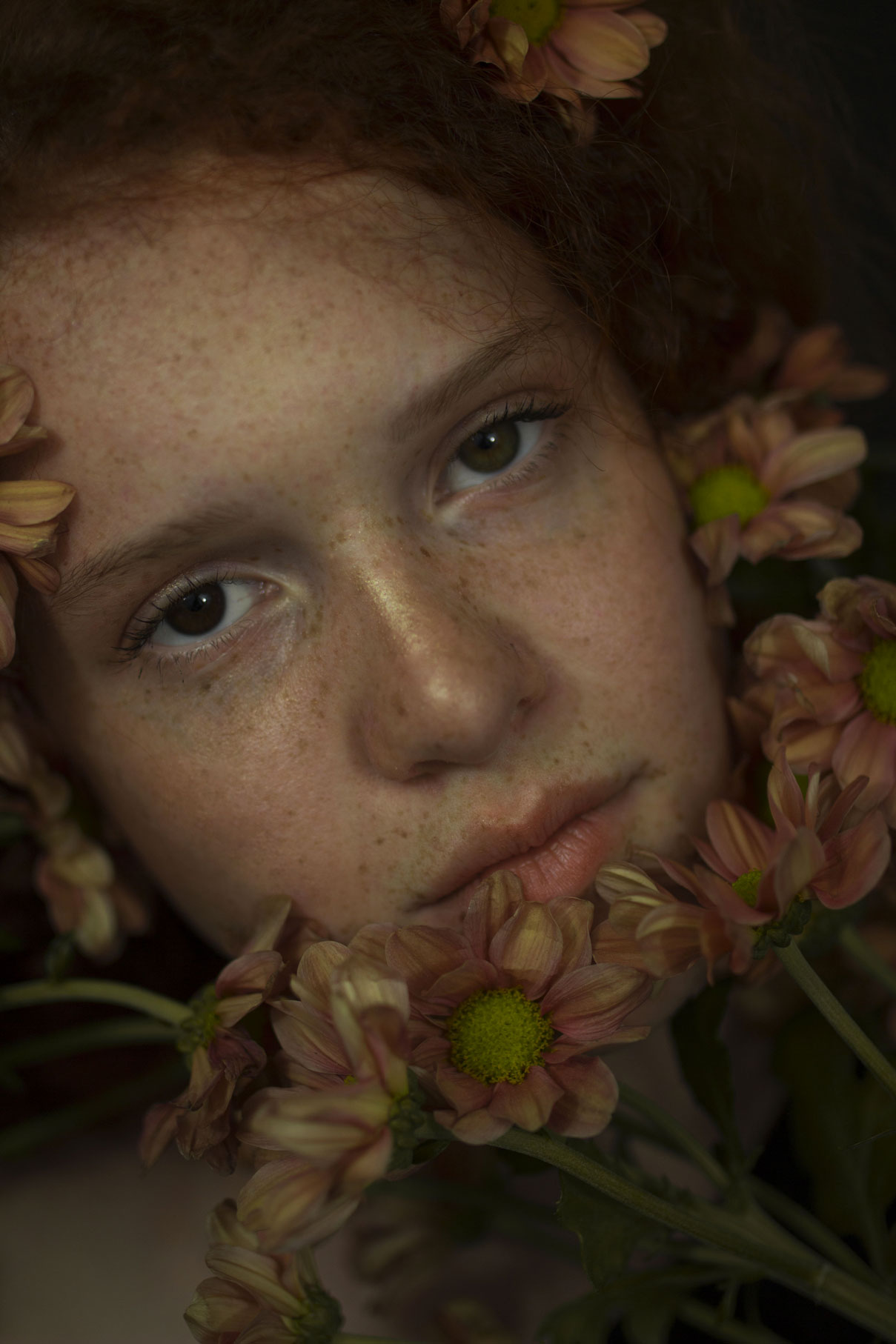 portrait d'une jeune fille rousse aux yeux verrons avec des tâches de rousseurs et des fleurs orangées