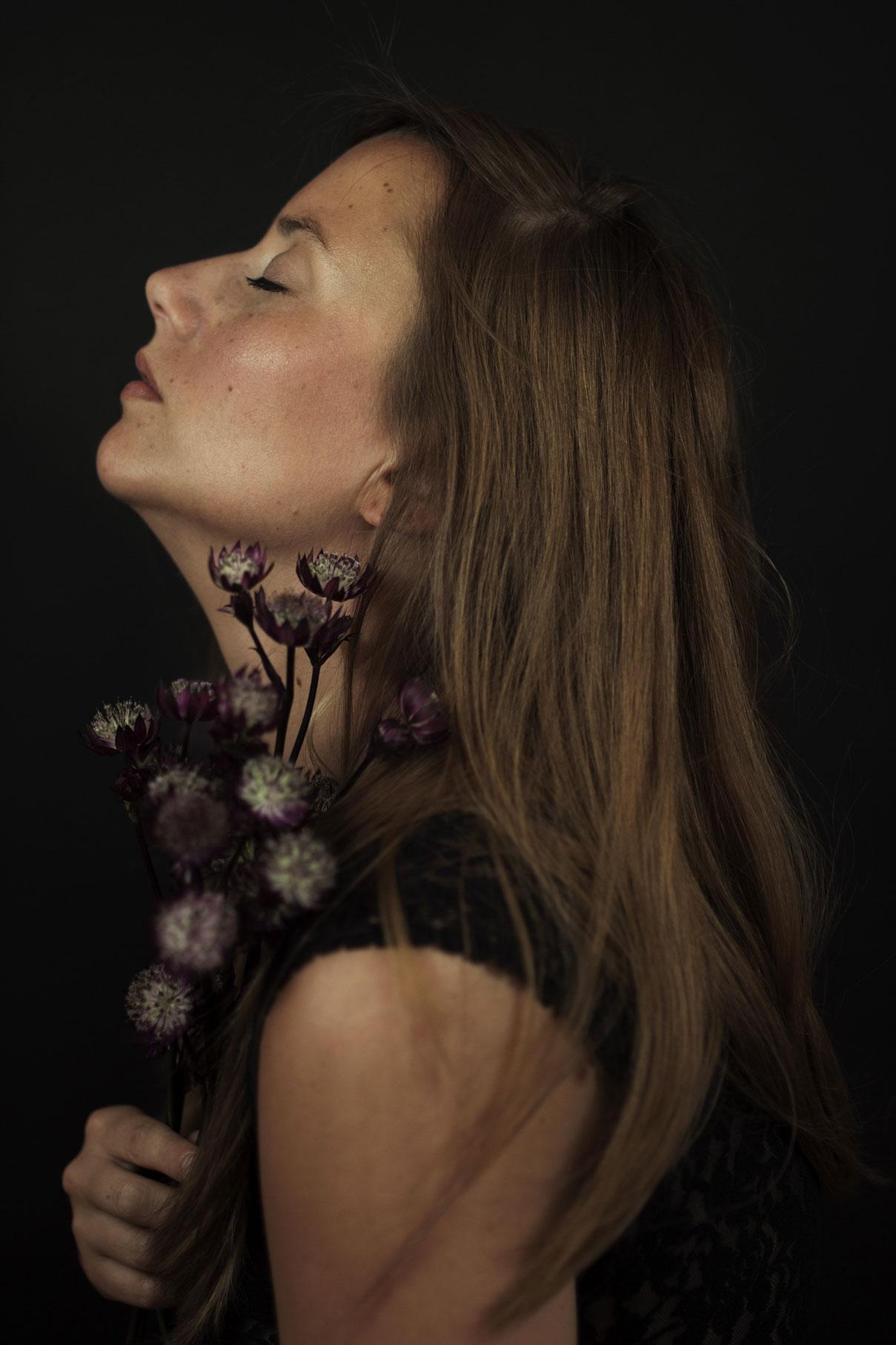 portrait d'une jeune femme de profil la tête en arrière avec un bouquet de fleurs