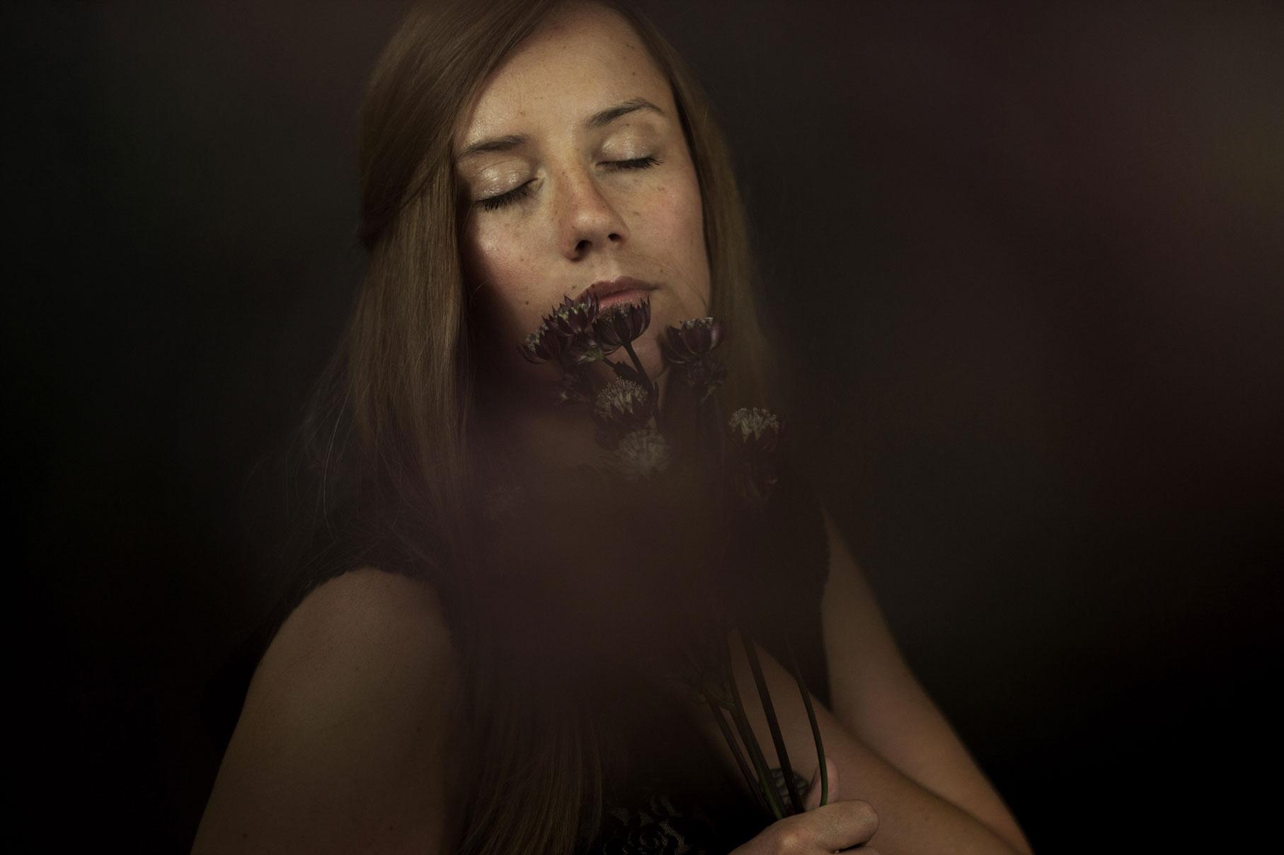portrait d'une jeune femme les yeux fermées avec un bouquet de fleurs, avec un effet de flou artistique