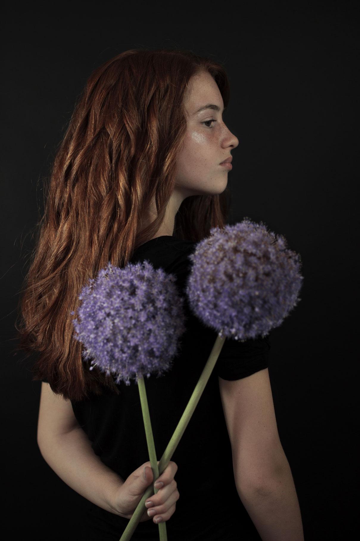jeune fille aux longs cheveux roux de dos avec deux grandes fleurs violettes