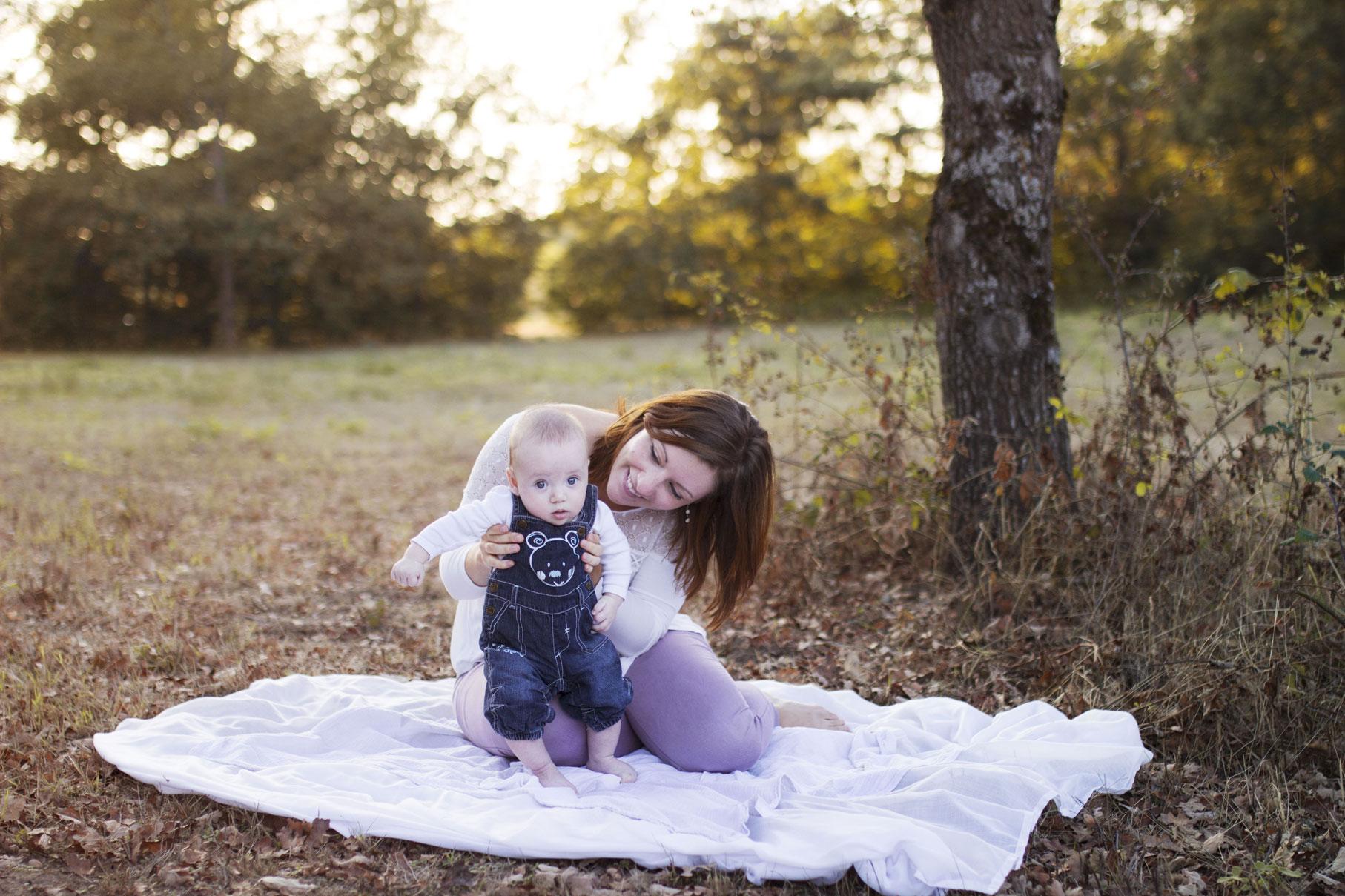 Cyrielle et son bébé Joshua au pied d'un arbre sur un drap blanc