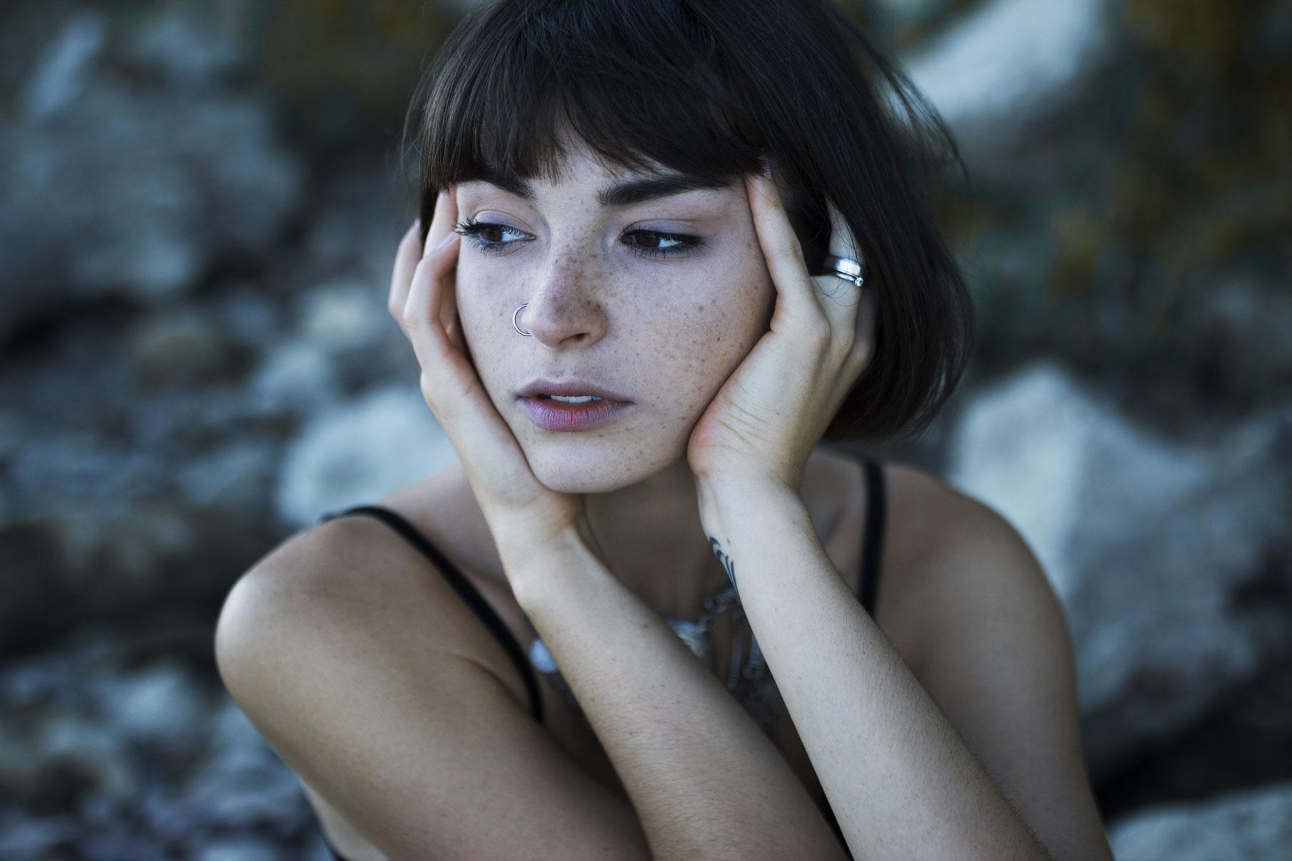Jeune femme aux cheveux au carré dans l'eau d'un fleuve avec des rochers