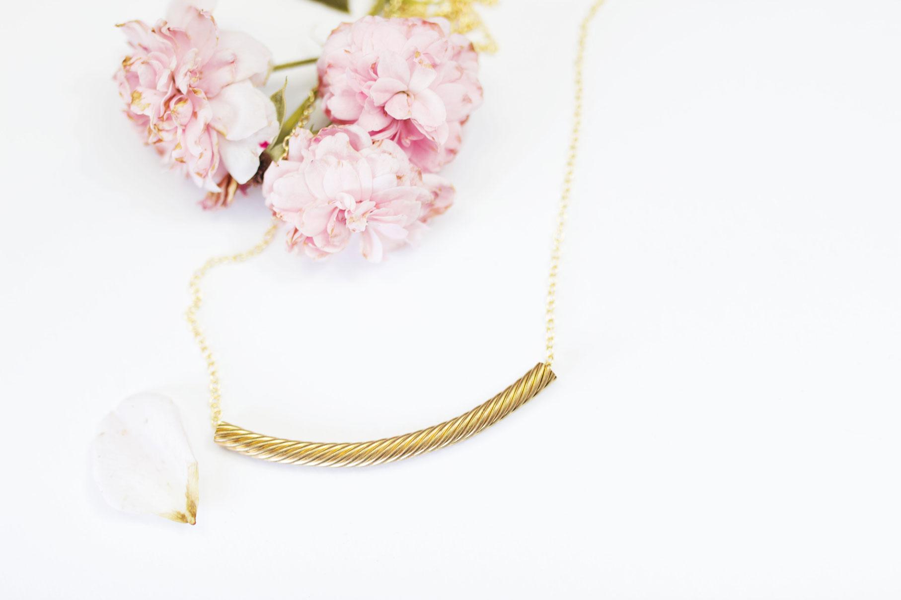 collier doré sur fond blanc avec fleurs roses