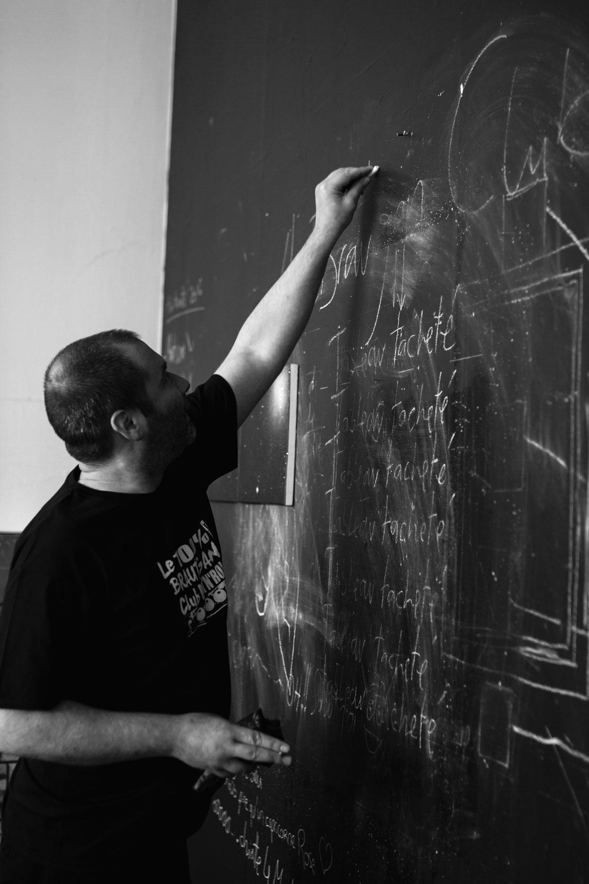 artiste illustrant un tableau noir pour les photos de promotion d'un groupe de rock français
