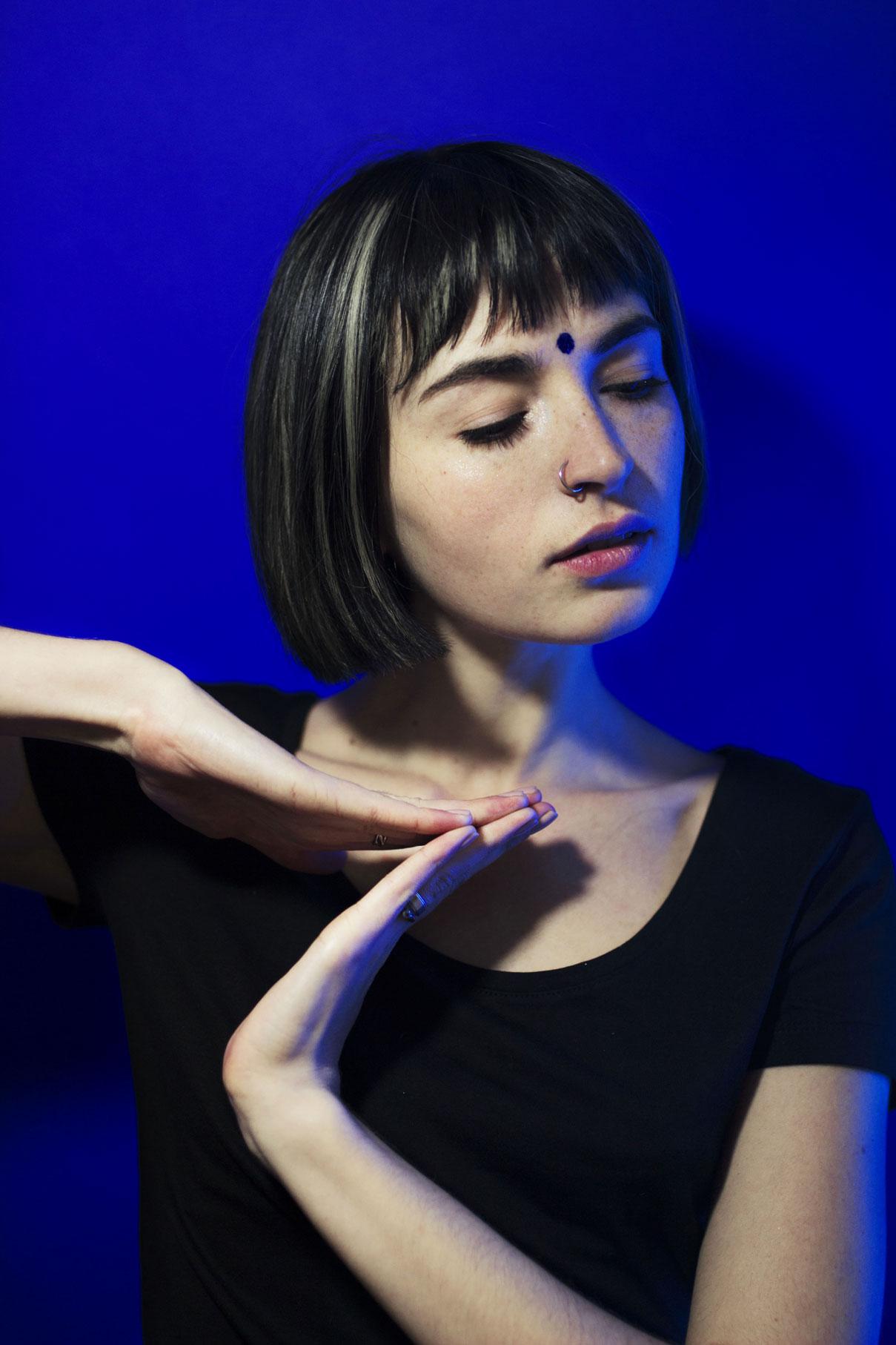 jeune femme dansant devant un fond bleu avec un bindi