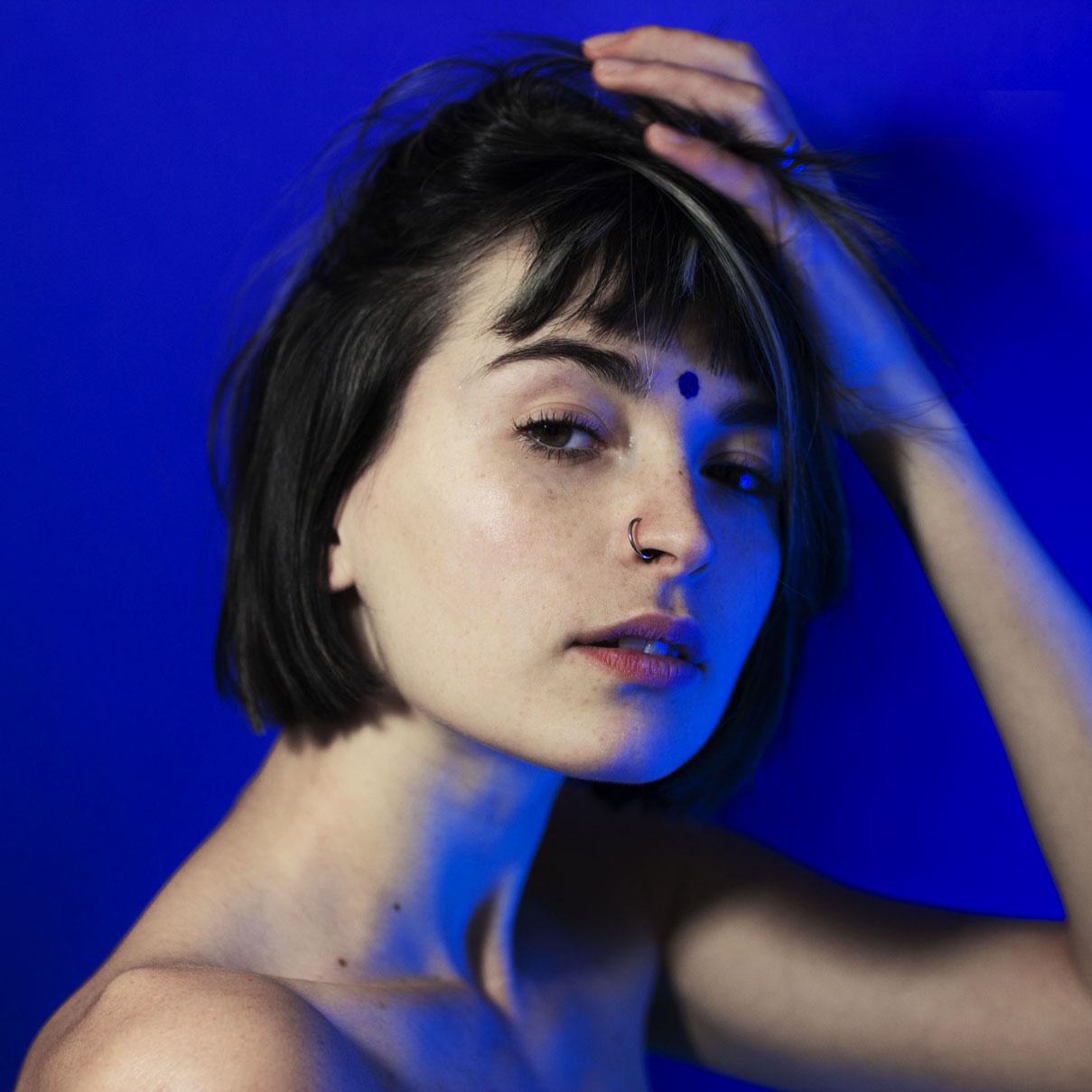 jeune femme portant un bindi bleu, sur fond bleu et éclairée par des néons bleus.