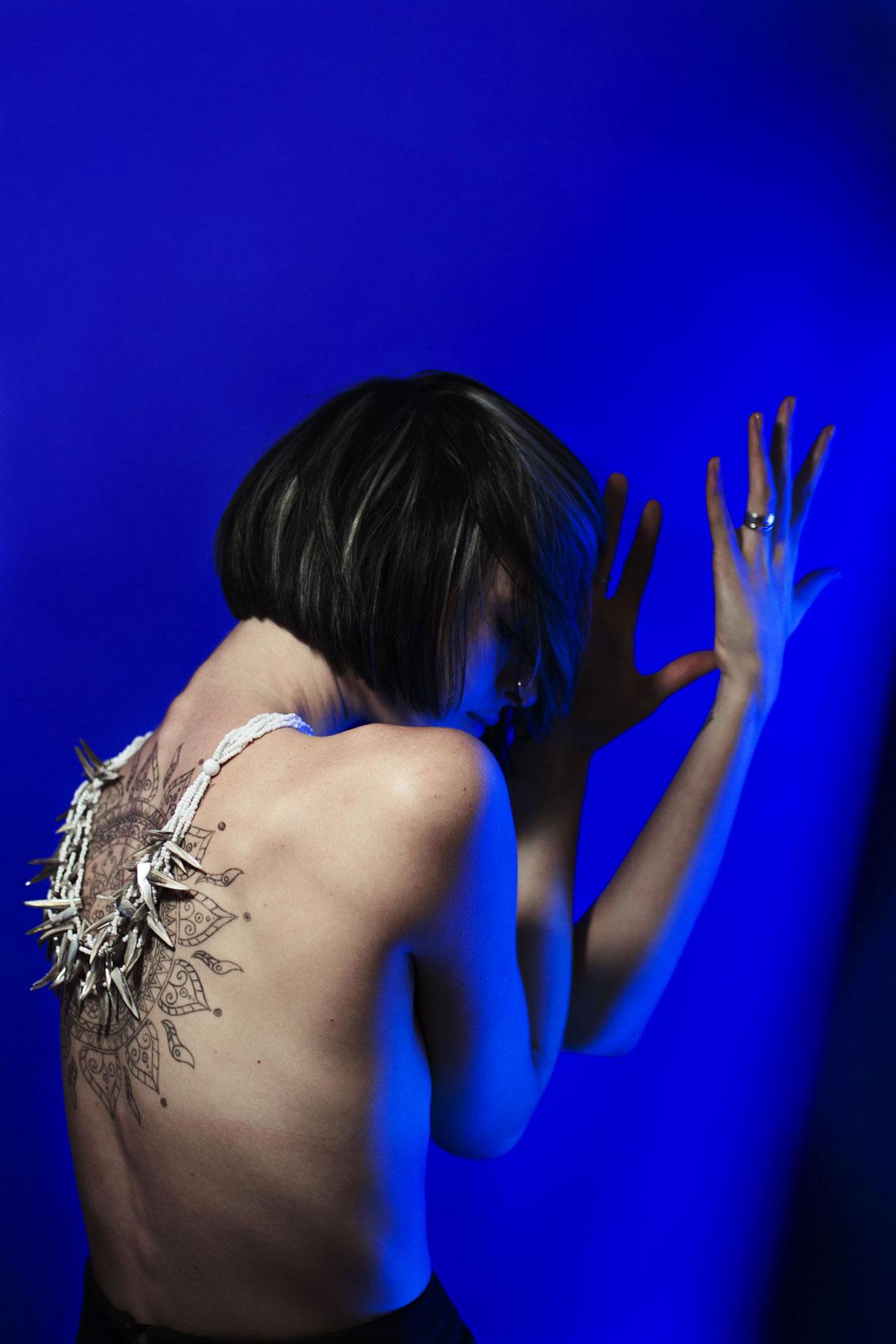 Jeune femme dos nu avec un tatouage tribal, devant un fond bleu et éclairée par des néons bleus.