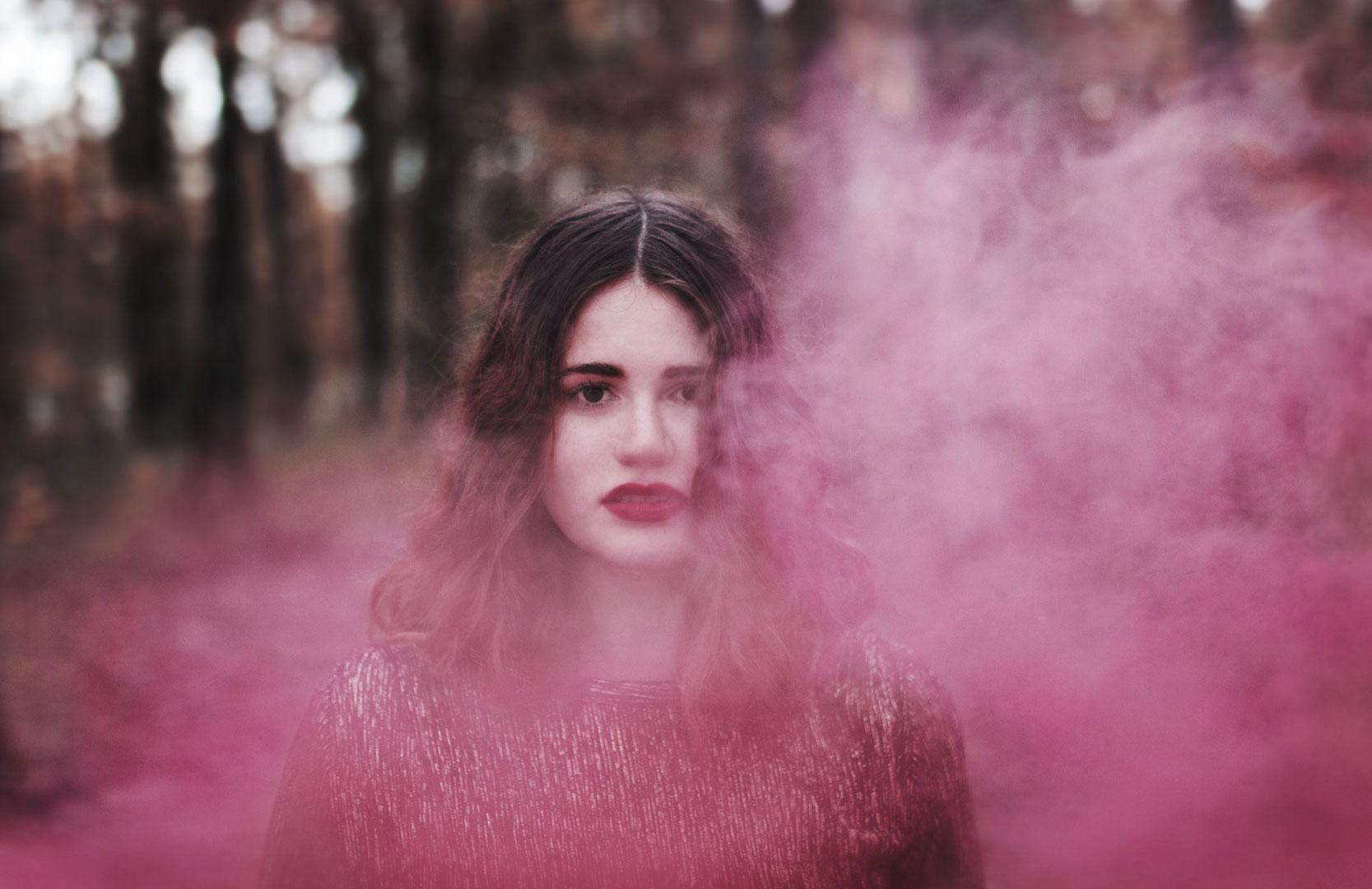Portrait d'une jeune fille rousse avec de la fumée rose