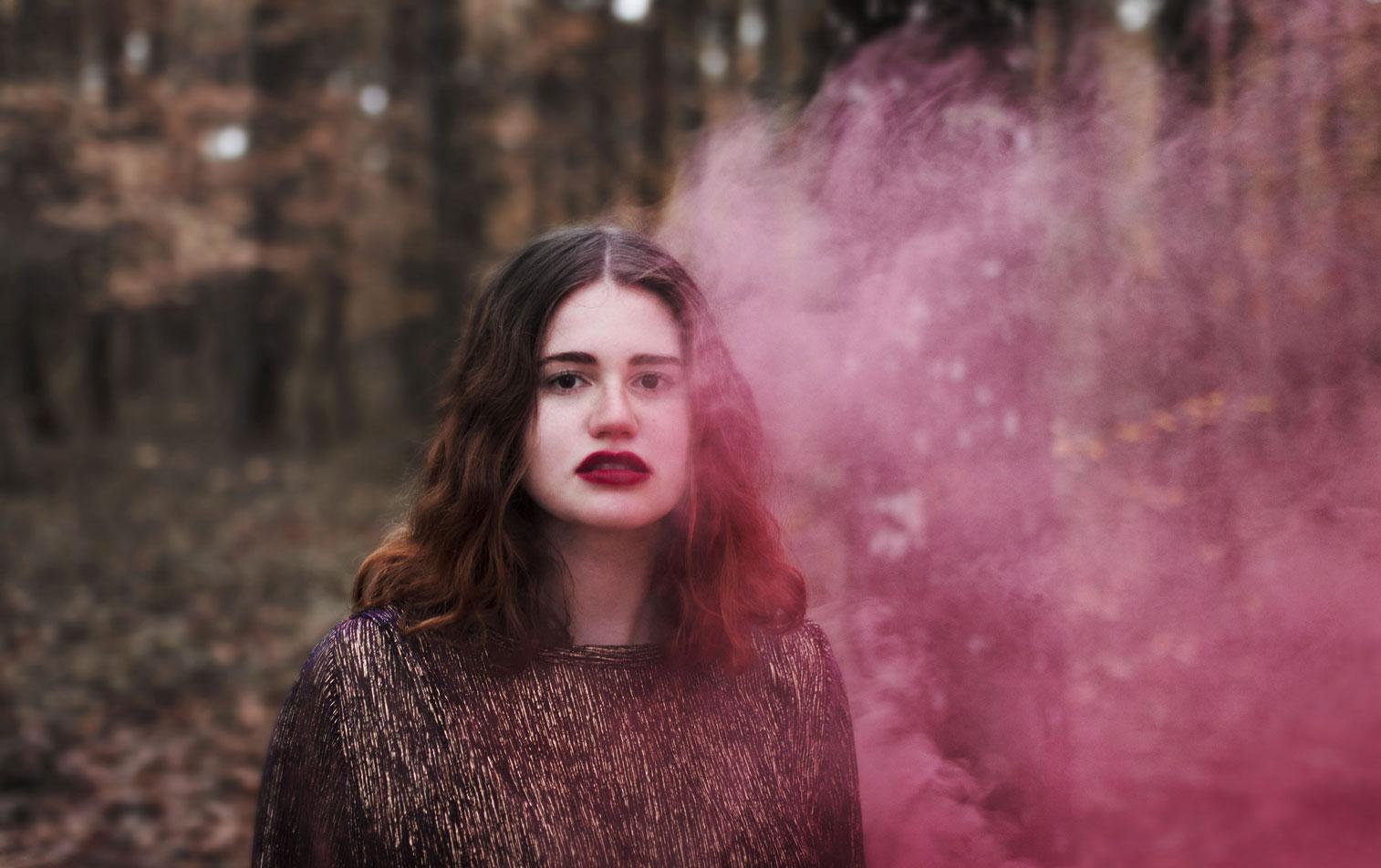 portrait d'une jeune fille rousse dans la foret à Tours, avec un fumigène rose.