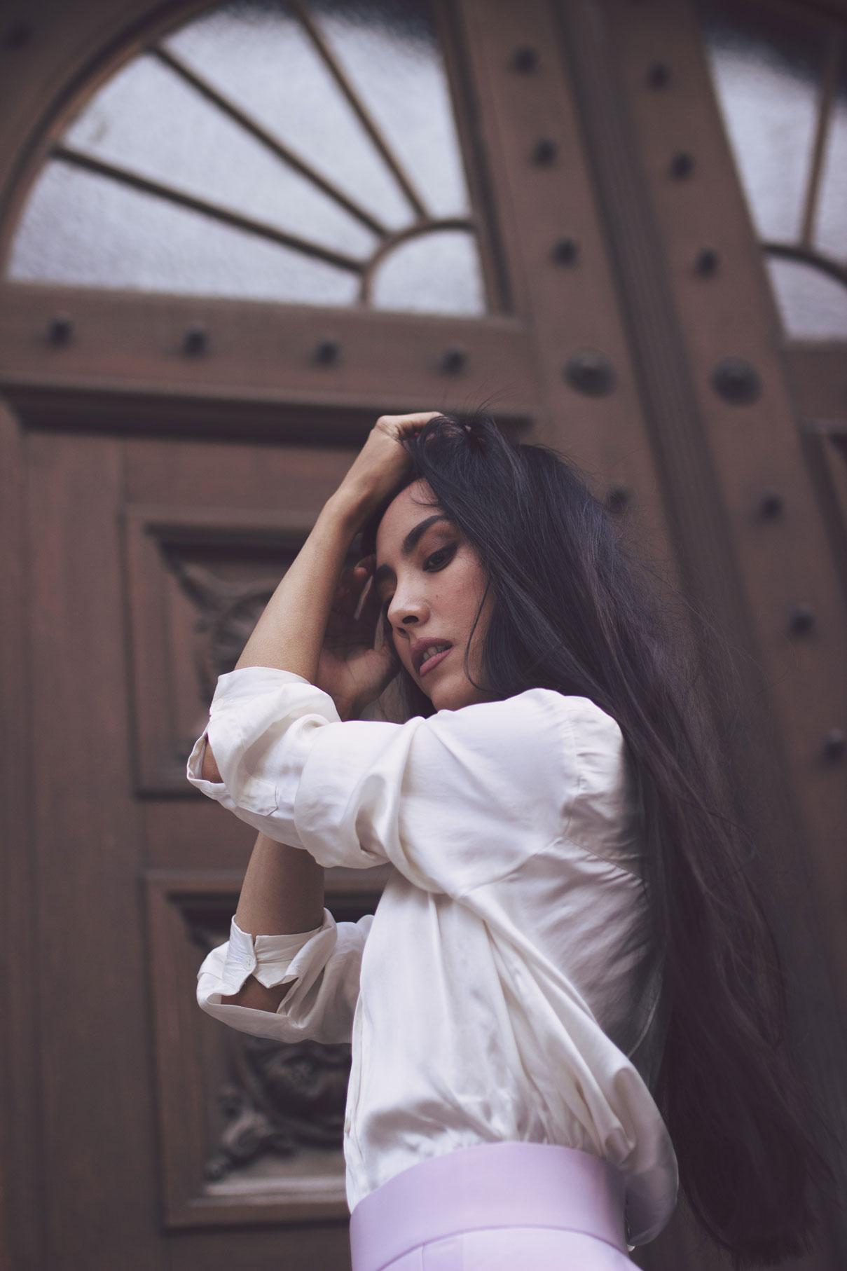 portrait d'une femme devant une porte en bois