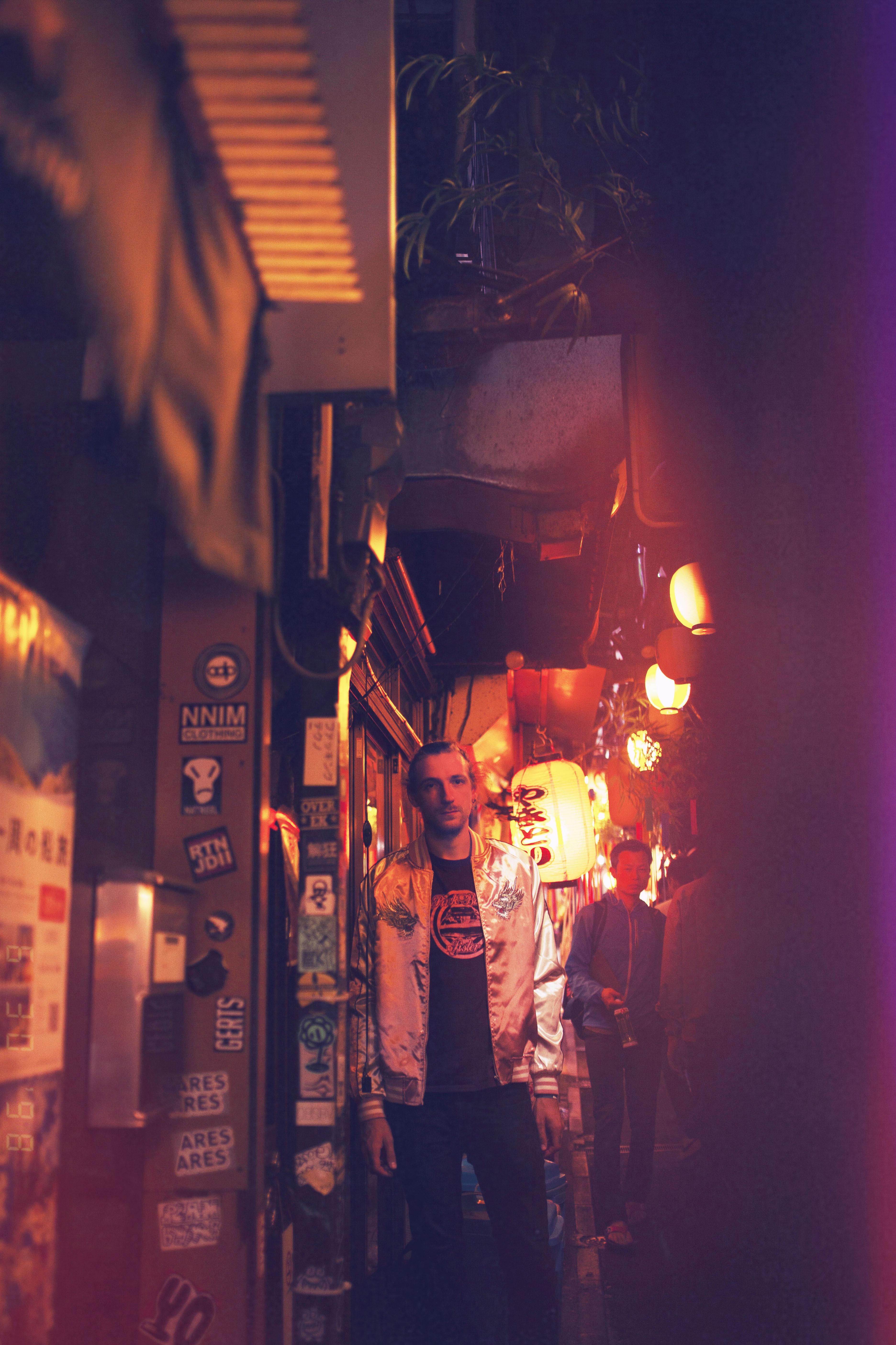 portrait d'un homme la nuit dans une rue japonaise